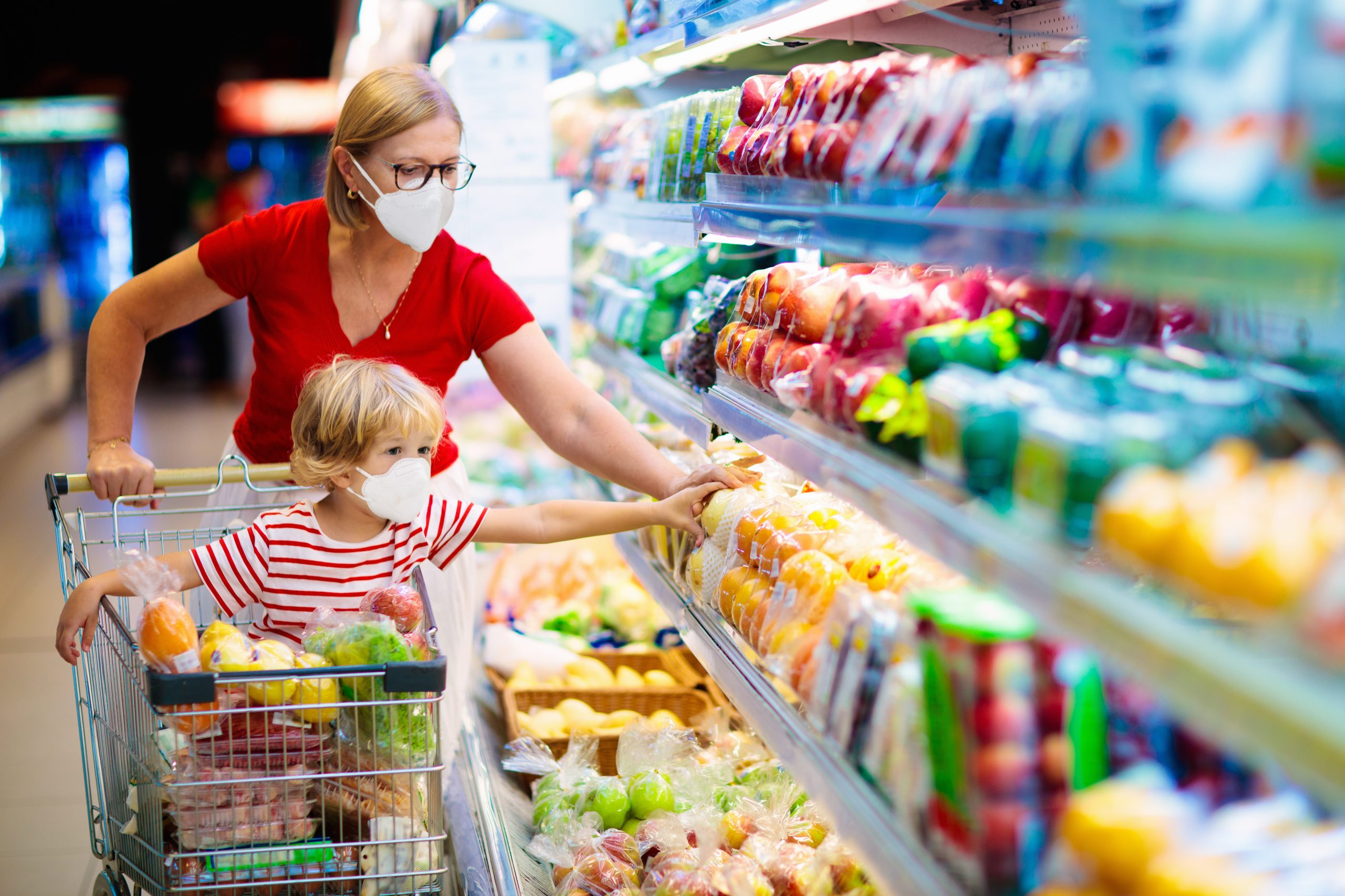 Mother and child buying fruit in supermarket.
