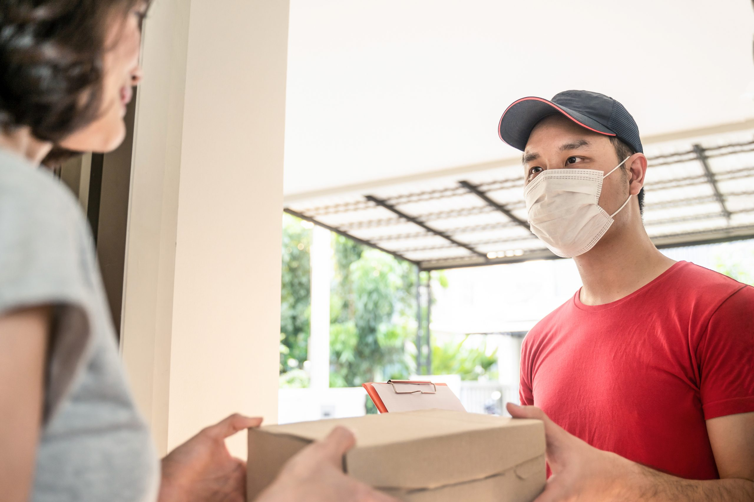 Asian postman or deliveryman carry small box deliver to young woman customer in front of door at home. Man wearing mask prevent covid or coranavirus affection outbreak. Social distancing work concept.