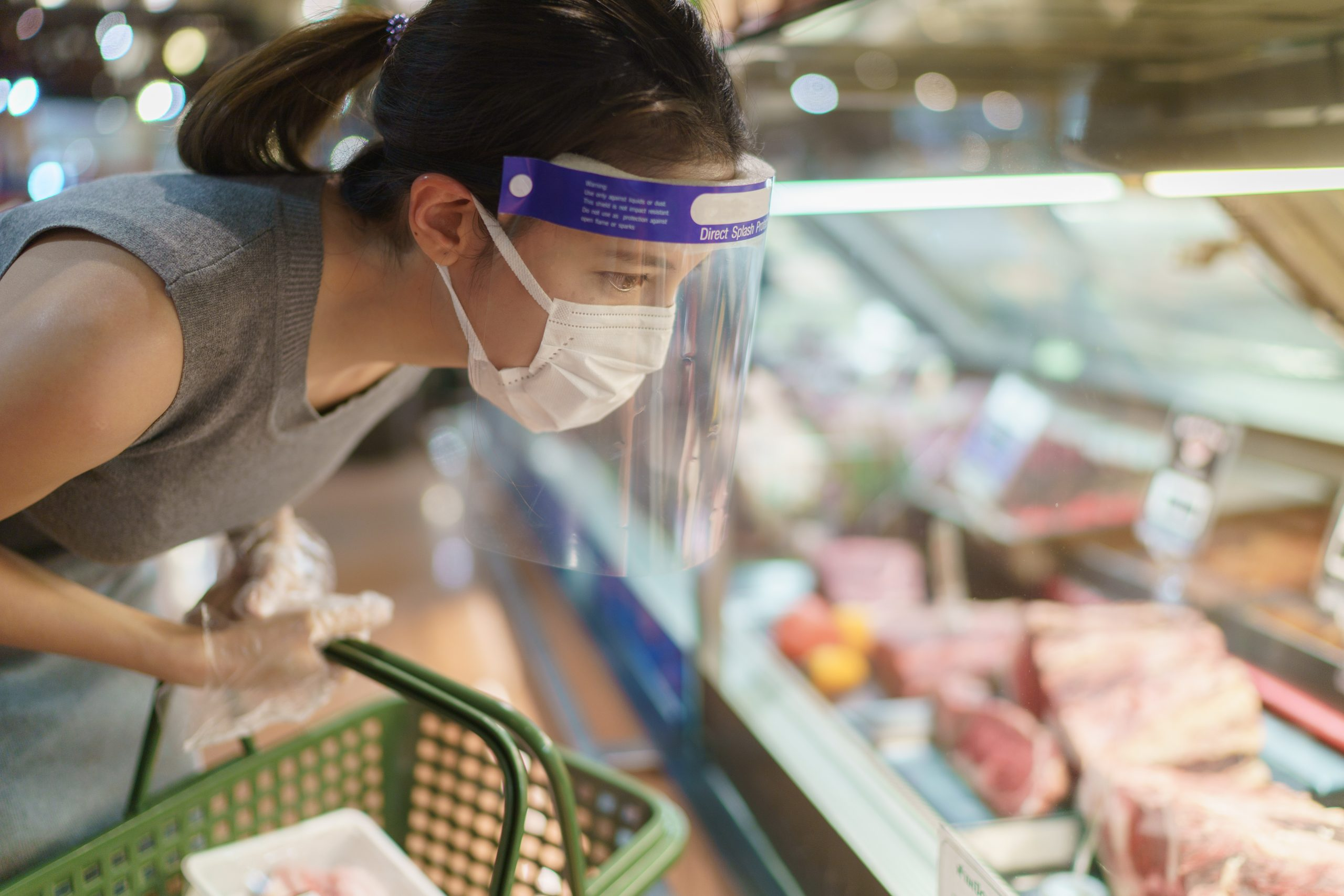 Woman wearing gloves, face shield and mask choosing meat at supermarket . Panic shopping during the corona virus pandemic.